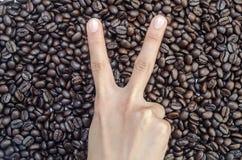 Hand ` 2 vinger ` op koffiebonen Royalty-vrije Stock Foto