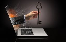 Hand with vintage huge key coming out of a laptop. With sparkling effects stock photo