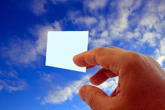Hand and visit card. Hand giving blank visit card on blue sky with clouds royalty free stock image