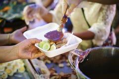 Hand-voedt aan behoeftig in de maatschappij: Concept het Voeden: De vrijwilligers geven voedsel aan de armen: het schenken van vo stock afbeeldingen