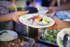 Hand-voedt aan behoeftig in de maatschappij: Concept het Voeden: De vrijwilligers geven voedsel aan de armen: het schenken van vo royalty-vrije stock afbeelding