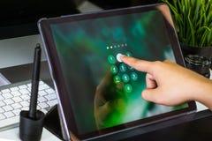 Hand von den Frauen, die Tablet-Computer mit Passwortanmeldung auf Geröll binden stockfoto