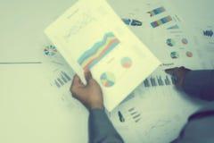 Hand von den jungen Geschäftsleuten, die Diagramm- und Diagrammdokument analysieren Lizenzfreies Stockfoto