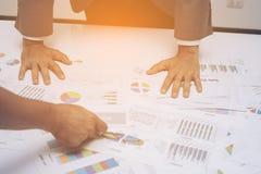 Hand von den jungen Geschäftsleuten, die Diagramm- und Diagrammdokument analysieren Stockfoto