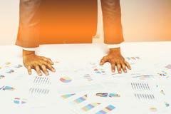 Hand von den jungen Geschäftsleuten, die Diagramm- und Diagrammdokument analysieren Stockbild