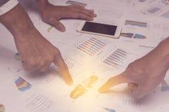Hand von den jungen Geschäftsleuten, die Diagramm- und Diagrammdokument analysieren Stockfotos