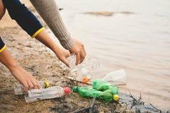 Hand von den Leuten, die leer vom Flaschenplastik aufheben Lizenzfreie Stockfotos