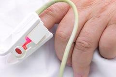 Hand von ernsthaft krankem mit Sauerstoffsättigungs-Sensor. Stockfoto