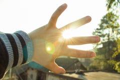 Hand vor Sonne Stockfoto