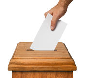 Hand voting. Hand putting a blank voting ballot into the box isolated on white background, clipping path Stock Image