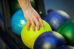 Hand wählt eine Bowlingkugel aus Lizenzfreies Stockbild