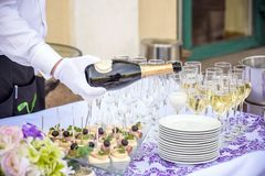 Hand of the waiter pours white wine in wineglass. Bright picture. Hand of the waiter pours white wine or champagne in wineglass. Bright picture of pouring wine Royalty Free Stock Image