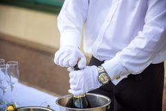 Hand of the waiter pours white wine in wineglass. Bright picture. Hand of the waiter pours white wine or champagne in wineglass. Bright picture of pouring wine Stock Photo