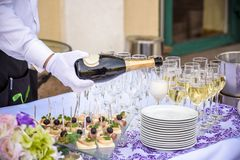 Hand of the waiter pours white wine in wineglass. Bright picture. Hand of the waiter pours white wine or champagne in wineglass. Bright picture of pouring wine royalty free stock photography