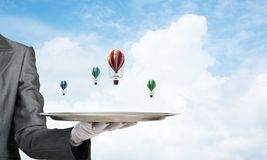 Hand of waiter presenting balloons on tray. Closeup of waiter`s hand in glove presenting flying aerostats on metal tray with blue cloudy skyscape on background Royalty Free Stock Photography