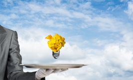 Hand of waiter presenting crampled paper lightbulb. Cropped image of waitress`s hand in white glove presenting crumpled paper lightbulb on metal tray with cloudy royalty free stock image