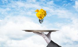 Hand of waiter presenting crampled paper lightbulb. Cropped image of waitress`s hand in white glove presenting crumpled paper lightbulb on metal tray with cloudy stock image