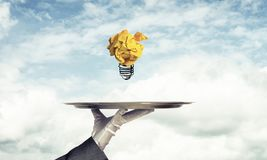 Hand of waiter presenting crampled paper lightbulb. Cropped image of waitress`s hand in white glove presenting crumpled paper lightbulb on metal tray with cloudy royalty free stock photos