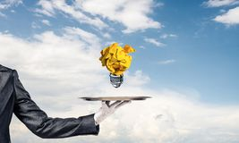 Hand of waiter presenting crampled paper lightbulb. Cropped image of waitress`s hand in white glove presenting crumpled paper lightbulb on metal tray with cloudy stock images