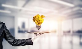 Hand of waiter presenting crampled paper lightbulb. Cropped image of waitress`s hand in white glove presenting crumpled paper lightbulb on metal tray with office royalty free stock image