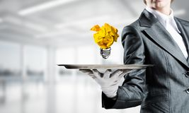 Hand of waiter presenting crampled paper lightbulb. Cropped image of waitress`s hand in white glove presenting crumpled paper lightbulb on metal tray with office stock image