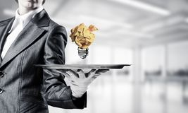 Hand of waiter presenting crampled paper lightbulb. Cropped image of waitress`s hand in white glove presenting crumpled paper lightbulb on metal tray with office stock photo