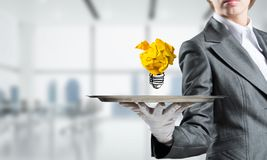 Hand of waiter presenting crampled paper lightbulb. Cropped image of waitress`s hand in white glove presenting crumpled paper lightbulb on metal tray with office royalty free stock photos