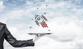 Hand of waiter presenting sketched rocket on tray. Cropped image of waitress`s hand in white glove presenting sketched flying missile on metal tray with cloudy stock image