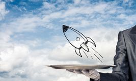 Hand of waiter presenting sketched rocket on tray. Cropped image of waitress`s hand in white glove presenting sketched flying missile on metal tray with cloudy royalty free stock photo