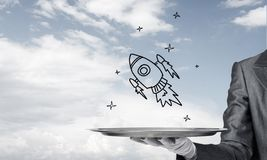 Hand of waiter presenting sketched rocket on tray. Cropped image of waitress`s hand in white glove presenting sketched flying missile on metal tray with cloudy royalty free stock image