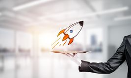 Hand of waiter presenting sketched rocket on tray. Cropped image of waitress`s hand in white glove presenting sketched flying missile on metal tray with office royalty free stock image