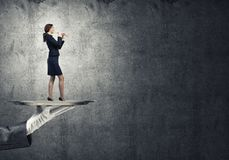 Attractive businesswoman on metal tray playing flute and concrete wall background Royalty Free Stock Photo