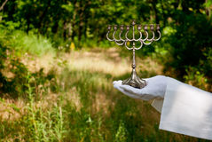 Hand of a waiter in a white glove holds a metal candlestick Jews in the nature Stock Images