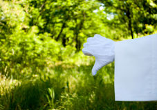 Hand of a waiter in a white glove showing a sign of a dislike against a nature background stock photography