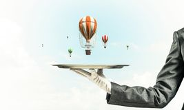 Hand of waitress presenting balloons on tray. Closeup of waitress`s hand in glove presenting flying aerostats on metal tray with blue cloudy skyscape on Stock Image