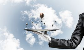 Hand of waitress presenting balloons on tray. Closeup of waitress`s hand in glove presenting flying aerostats on metal tray with blue cloudy skyscape on Stock Photo