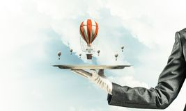 Hand of waitress presenting balloons on tray. Closeup of waitress`s hand in glove presenting flying aerostats on metal tray with blue cloudy skyscape on Royalty Free Stock Image