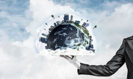 Hand of waitress presenting Earth globe on tray. Cropped image of waitress`s hand in white glove presenting Earth globe on metal tray with cloudy skyscape on Royalty Free Stock Photo