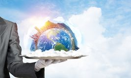 Hand of waitress presenting Earth globe on tray. Cropped image of waitress`s hand in white glove presenting Earth globe on metal tray with cloudy skyscape on stock photos
