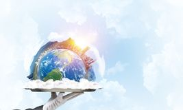 Hand of waitress presenting Earth globe on tray. Cropped image of waitress`s hand in white glove presenting Earth globe on metal tray with cloudy skyscape on royalty free stock photography