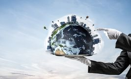 Hand of waitress presenting Earth globe on tray. Cropped image of waitress`s hand in white glove presenting Earth globe on metal tray and pointing on it with royalty free stock image