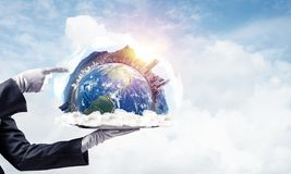 Hand of waitress presenting Earth globe on tray. Cropped image of waitress`s hand in white glove presenting Earth globe on metal tray and pointing on it with royalty free stock images