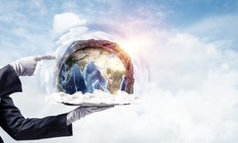 Hand of waitress presenting Earth globe on tray. Cropped image of waitress`s hand in white glove presenting Earth globe on metal tray and pointing on it with royalty free stock photography