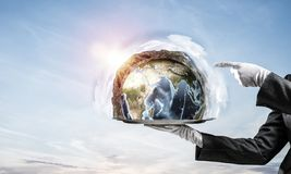 Hand of waitress presenting Earth globe on tray. Cropped image of waitress`s hand in white glove presenting Earth globe on metal tray and pointing on it with stock photo