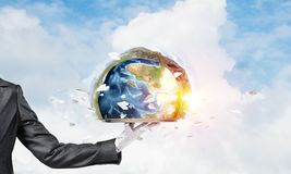 Hand of waitress presenting Earth globe on tray. Cropped image of waitress`s hand in white glove presenting Earth globe on metal tray with cloudy skyscape on royalty free stock image