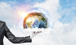 Hand of waitress presenting Earth globe on tray. Cropped image of waitress`s hand in white glove presenting Earth globe on metal tray with cloudy skyscape on Stock Images