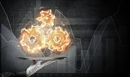 Hand of waitress presenting flaming cogwheels. Cropped image of waitress`s hand in white glove presenting flaming cogwheels structure on metal tray with dark Stock Image
