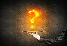 Hand of waitress presenting flaming question mark Stock Photo