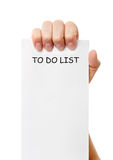 Hand was holding of a to do list paper note. Isolated on white background Stock Image