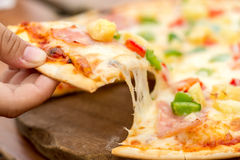 Hand was pulling a pizza out. Pizza with sausage, tomatoes, mushrooms and cheese close up. background Royalty Free Stock Photo